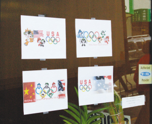 图为华埠民众在公司外玻璃上张贴自己设计的北京奥运会海报。(美国《侨报》/刘海平 摄)
