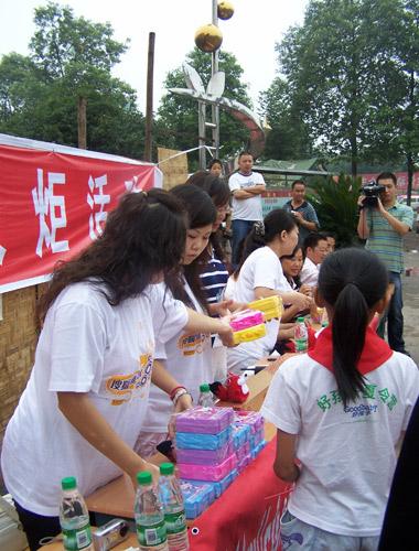 搜狐新闻社区的志愿者为孩子们发放带来的文具