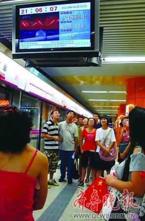 乘 客 们 在 地 铁 站 观 看 开 幕 式