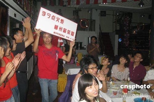 8月8日晚,当李宁点燃北京奥运主火炬一刻,他的故乡广西柳州全城沸腾,酒吧里市民为奥运加油助威,掌声久久不歇。 中新社发 蒙鸣明 摄