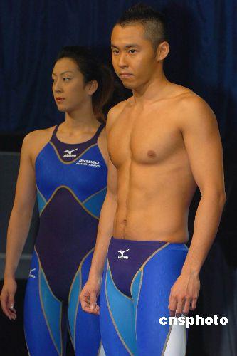 """6月1日下午,日本著名运动服装品牌""""美津浓""""举行今夏新款泳装发布会,日本著名男子游泳名将北岛康介加盟助兴,在T台上也秀了一回。图为北岛康介展示美津浓公司最新设计的比赛用泳衣。 中新社发 滕剑峰 摄"""
