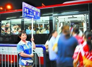 公交志愿者手举引导牌为参加北京奥运会开幕式的观众提供乘车方便。  本报特约摄影 刁立声