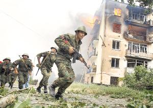 8月9日,在格鲁吉亚南奥塞梯首府茨欣瓦利附近的哥里市,一些格鲁吉亚士兵从一座遭袭击起火的楼房旁边跑过。 新华社/路透