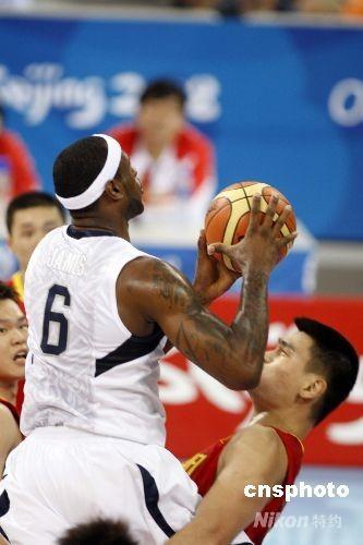 """8月10日,奥运男子篮球比赛中国男篮与美国男篮在北京五棵松篮球馆正式开打,图为美国6号队员詹姆斯""""攻克""""姚明的防守。 中新社发 盛佳鹏 摄"""