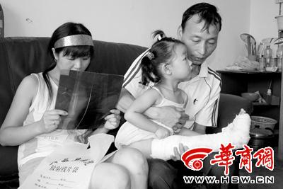 夫妇俩抱着右腿骨折的女儿愁眉紧锁