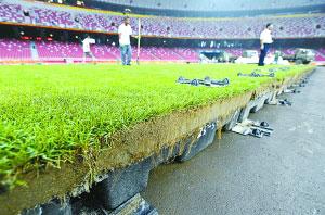 10日,工作人员在鸟巢铺设草坪。9日凌晨至12日中午,奥运会开幕式设备须拆除,同时安装好闭幕式设备。 新华社发