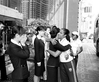 沈阳奥运村皇朝万豪酒店,工作人员与巴西女足队员相拥,为她们送别。特约记者宇航摄