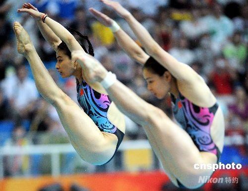 8月10日,中国跳水选手郭晶晶(后)、吴敏霞在奥运会女子3米双人跳板比赛中。两人顺利摘下了该项目金牌,这是中国跳水队在北京奥运的第一面金牌,也是中国兵团的第四面金牌。 中新社发 CNAsports 摄