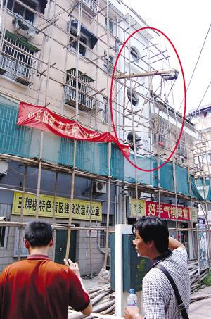 吊机从屋顶坠落,被脚手架卡住。