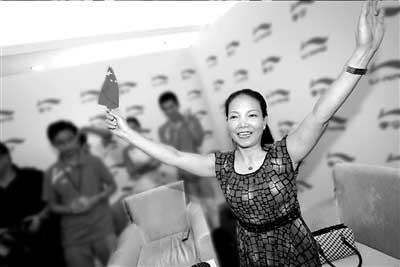 在中国队获得冠军后李小鹏母亲高兴地挥舞国旗。本报记者张沫摄