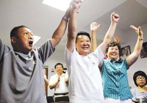 黄旭的启蒙教练赵振民(左一)和黄旭的父母看到中国男子体操队登上领奖台时振臂欢呼 新华社发