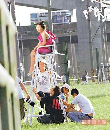 她(上)坐在高脚楼椅上惬意哼歌,多名工作人员在旁小心扶椅护花