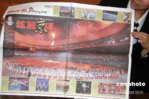 """8月9日出版的台湾各大报纸,纷纷以头版、专刊报道北京奥运会开幕式的盛况。图为《联合报》将平日的A1版与相连的版面打通,""""炫丽京叹""""的醒目标题及超大彩色照片,给人强烈的视觉冲力。 中新社发 董会峰 摄"""