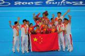 图文:体操女团夺金 队员教练与国旗一起合影