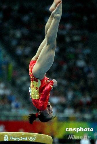 """8月13日上午,北京奥运会女子体操团体决赛在北京奥林匹克公园内的国家体育馆举行,由程菲、杨伊琳、江钰源、何可欣、李珊珊、邓琳琳组成的中国女队,向金牌发起冲击。中国队首先从跳马比赛开始,图为程菲从""""程菲跳""""开始向金牌冲击。 中新社发 任晨鸣 摄"""
