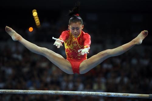 8月13日,中国选手江钰源在进行高低杠比赛。当日,在国家体育馆举行的北京奥运会体操女子团体决赛中,中国队以188.900分的成绩夺得冠军。