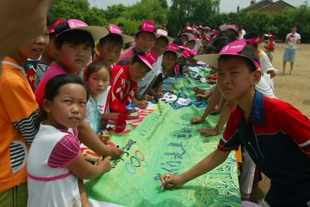 孩子们兴奋地在横幅上签名祝福奥运