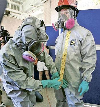 香港消防处救护员配备防生化及核事故装备,防化衣需用胶条封住,以保证不会渗漏。(图片来源:明报)