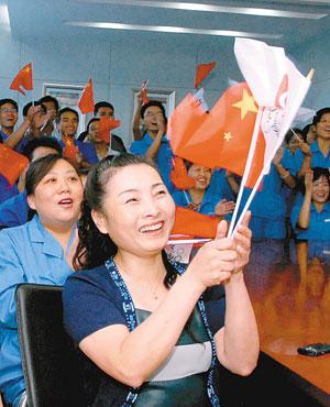 秦凯妈妈挥舞国旗为儿子加油喝彩 记者 冯炜 刘寅摄