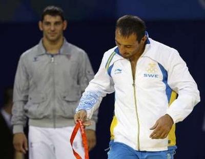 8月14日,意大利选手明古齐获得金牌后情不自禁亲吻礼仪小姐。(本图片来源为国际在线)