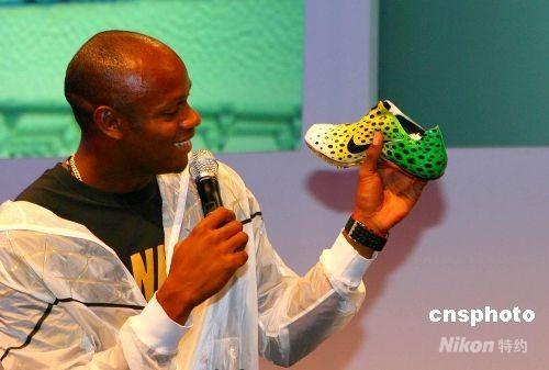8月12日夜,世界短跑名将鲍威尔与耐克共同在北京发布第一双采用Nike Flywire技术制作的强力短跑钉鞋,鲍威尔本人参与该跑鞋的设计过程。图为他在展示该跑鞋。 中新社发 沈晨 摄