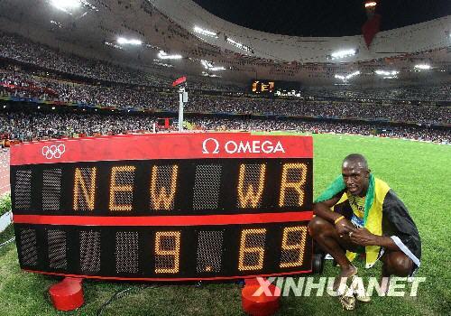"""8月16日,牙买加选手尤塞恩·博尔特在比赛后与计时器合影。当日,博尔特在国家体育场""""鸟巢""""进行的北京奥运会男子100米决赛中以9秒69的成绩夺得金牌并打破9秒72的世界纪录。 新华社记者廖宇杰摄"""