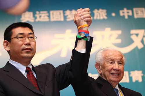 奥组委志愿者部部长刘剑为萨马兰奇佩戴微笑圈