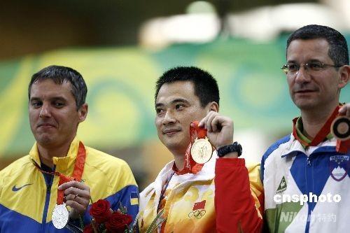 """8月17日,北京射击馆迎来奥运会射击比赛的最后一天,在男子50米步枪三种姿势的决赛中,美国选手埃蒙斯在前九枪取得巨大领先的情况下最后一枪仅打出4.4环的成绩将冠军拱手送给了中国选手邱健,中国选手邱健以1272.5环意外""""捡""""到一枚金牌,这也是中国射击队的第五块金牌,同时也是中国代表团在本届奥运会上的第28枚金牌。乌克兰选手苏霍鲁科夫以1272.4环获得银牌,世界纪录保持者斯洛文尼亚选手德贝韦茨获得一枚铜牌,成绩为1271.7环。 中新社发 盛佳鹏 摄"""