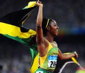 图文:牙买加女飞人百米摘金 身披国旗在奔跑中