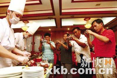 在北京和平门全聚德烤鸭店,热腾腾的烤鸭端上来了,这几位奥运工程的建设者掏出数码相机狂拍。
