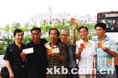 画家苏坚和四位农民工以及愿意为他们提供住房的李先生(左一)在鸟巢前合影留念。