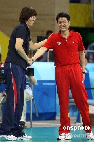 """8月15日晚,北京奥运会女排小组赛中国与美国之战在北京奥运会排球比赛馆--首都体育馆举行,这场被戏称为""""和平大战""""的比赛最后时刻,两名美国选手封死了中国队王一梅的扣杀而以3比2战胜中国女排。赛后,美国队主教练郎平主动上前与中国队主教练陈忠和握手。 中新社发 任晨鸣 摄"""