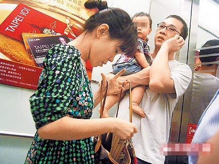 搭电梯时,彭佳慧老公(右)讲手机搞神秘,一旁的她面露不悦、低头整理包包