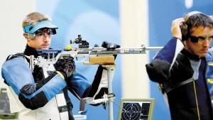 8月17日,在北京奥运会射击男子50米步枪三种姿势决赛中,美国选手埃蒙斯(左)在一路领先的情况下最后一枪打出4.4环,痛失金牌,获得第四名。中国选手邱健(上)获得冠军后与中国射击队总教练王义夫(下)挥手向观众致意。(新 华)