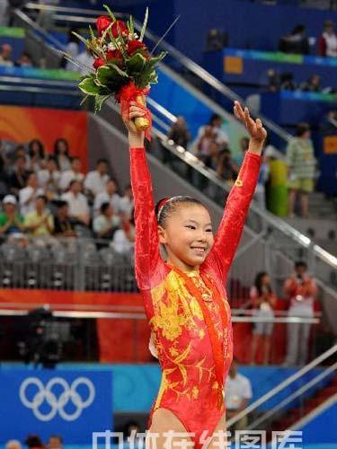 图文:女子高低杠决赛何可欣摘金 高举鲜花