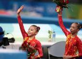 图文:何可欣夺得高低杠冠军 与杨伊琳挥手致意