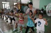 图文:林丹夺冠激励母校小学员 认真练习羽毛球