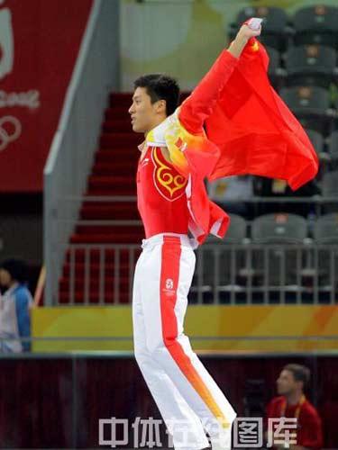 图文:男子蹦床陆春龙夺冠 跃起挥舞国旗