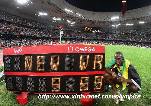 """新华社照片,北京,2008年8月16日 (北京奥运)(32)田径——尤塞恩·博尔特夺金 8月16日,牙买加选手尤塞恩·博尔特在比赛后与计时器合影。当日,博尔特在国家体育场""""鸟巢""""进行的北京奥运会男子100米决赛中以9秒69的成绩夺得金牌并打破9秒72的世界纪录。 新华社记者廖宇杰摄"""