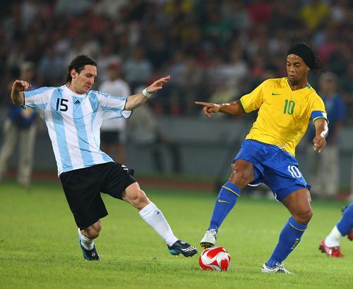 8月19日,阿根廷队球员梅西(左)和巴西队球员罗纳尔迪尼奥在拼抢。新华社记者龚兵摄