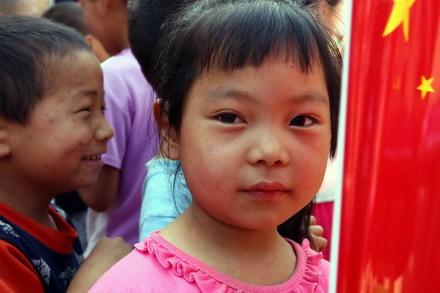 在国旗的映衬下,孩子们的严重充满了对未来的希望