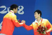 图文:男子3米跳板颁奖 季军中国秦凯握手祝贺