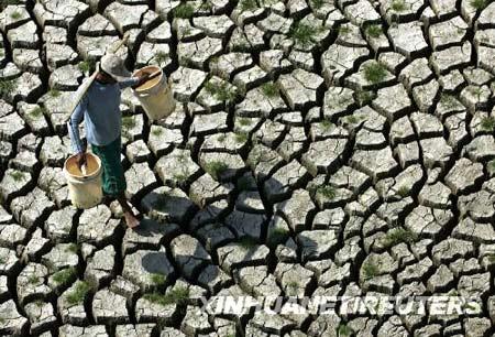8月20日,在印度尼西亚东爪哇省的拉蒙岸,为牲畜取水的村民手持空桶走过干涸的水坝。新华社/路透