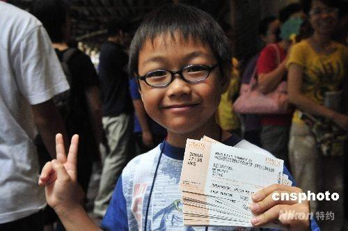 中国金牌运动员将访问香港三日,期间会有五场示范表演和汇演。八月二十一早上十时起开始销售门票。图为排头位的姓何小朋友购得多张门票,十分兴奋。他于清晨五时许便与家人在铜锣湾一票点排队够票。 中新社发 谭达明 摄