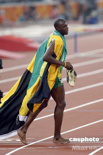 """8月20日晚,即将于8月21日迎来22岁生日的牙买加选手尤塞恩·博尔特在国家体育场鸟巢再造神话,在北京奥运会男子200米决赛中,以19秒30获得金牌,并打破约翰逊保持12年之久的19秒32的世界纪录。这是继博尔特16日晚以9秒69打破男子100米世界纪录后,再一次在""""鸟巢""""创造奇迹。荷属安的列斯选手许兰迪·马丁那以19秒82获得银牌,卫冕冠军美国选手肖恩·克劳福德以19秒96获得铜牌。 中新社发 盛佳鹏 摄"""