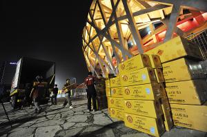 """昨天,工人将烟花搬上""""鸟巢""""顶部,今晚,8000枚烟花将点亮奥运会闭幕式主会场。赵鑫月/摄"""