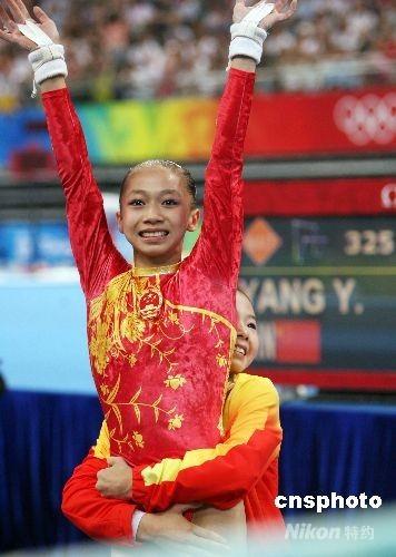 8月18日,中国选手何可欣在北京奥运会高低杠决赛中16.725分的成绩夺得金牌,队友杨伊琳摘铜。图为何可欣将杨伊琳抱起庆祝。 中新社发 武仲林 摄