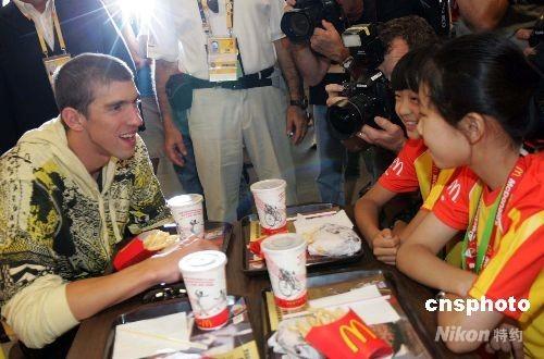 """2008年8月18日,奥林匹克公园餐厅内,菲尔普斯小朋友交谈。当日,获得8枚奥运金牌的美国游泳冠军菲尔普斯来到奥林匹克公园餐厅与40多名中外各国的""""奥运助威小冠军""""见面交流,与小朋友们一起分享胜利的喜悦。 中新社发 晓村 摄"""