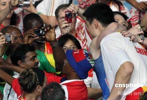 """8月24日晚,北京奥运会闭幕式在奥林匹克公园内的国家体育场""""鸟巢""""举行,经历了激烈鏖战的世界各地运动员在""""鸟巢""""内享受狂欢与快乐。图为澳大利亚女篮队长劳伦·杰克逊与姚明拥抱热吻。 中新社发 任晨鸣 摄"""
