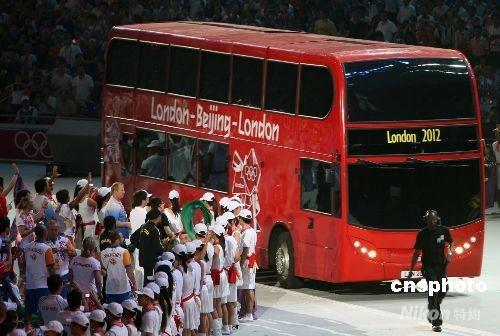 """8月24日晚,北京奥运会闭幕式在奥林匹克公园内的国家体育场举行,下届奥运会主办城市伦敦市上演""""伦敦8分钟""""演出,一辆伦敦标志性的双层红色巴士驶入""""鸟巢""""体育场。 中新社发 任晨鸣 摄"""